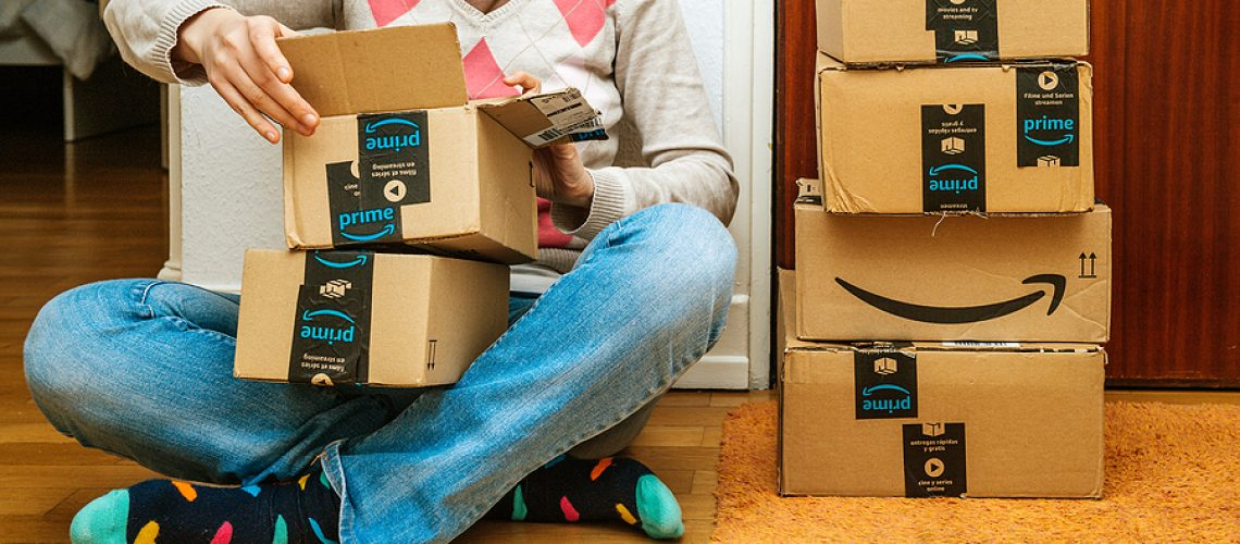 PARIS, FRANCE - JAN 13, 2018: Stack of Amazon Prime packages delivered to a home door woman unboxing unpacking the gift parcel boxes